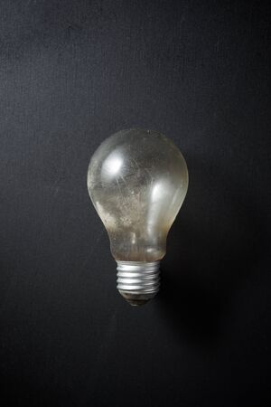 Photo for An old incandescent bulb on a black table. - Royalty Free Image