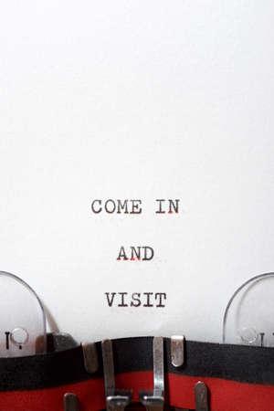 Foto de Come in and visit phrase written with a typewriter. - Imagen libre de derechos