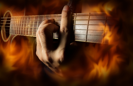Playing acoustic guitar with fire flame screen,music concept.