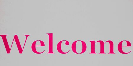 Welcome sign - pink lettering on a white background