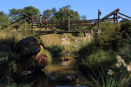 A tranquil country stream with a wooden bridge and blue sky in landscape format