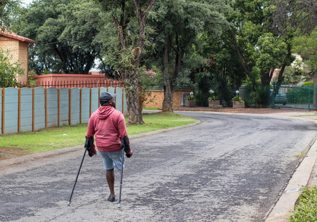 Johannesburg, South Africa - unidentified physically disabled man on crutches struggle through the streets of the city, image in landscape format
