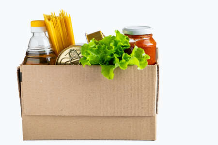 Photo pour Donation box with food on a white background. Delivery of essential foodstuffs. Place for text. - image libre de droit