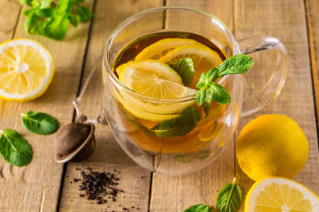 Photo pour Herbal tea with lemon and mint on a wooden background. Delicious drink for relaxation and alternative therapy of diseases. - image libre de droit