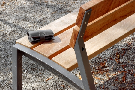 Black mens wallet lying outdoors on a wooden bench
