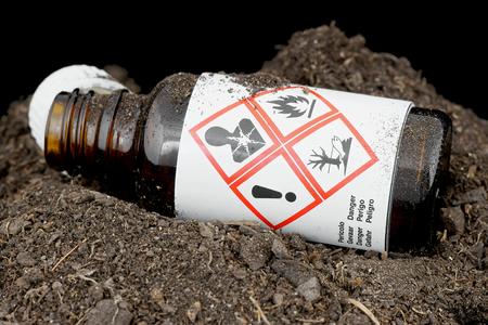 Bottle with hazardous waste thrown in the ground.の素材 [FY31042485091]
