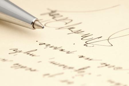 A handwritten message with a handwritten signature and a pen