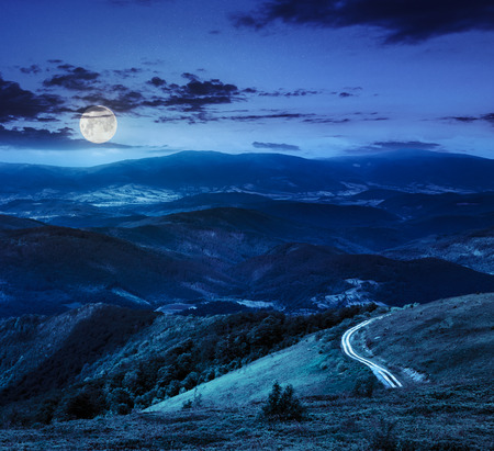 mountain range summer landscape. valley with stones and road on the hillside. forest on the mountain under the beam of light falls on a clearing at the top of the hill at night in moon light