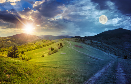 Foto de day and night collage landscape. fence near the meadow path on the hillside. village near forest in mountains with sun and full moon - Imagen libre de derechos