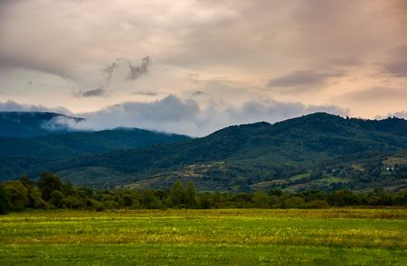 dawn in mountainous countryside. clouds rising above the hills. lovely autumn landscape