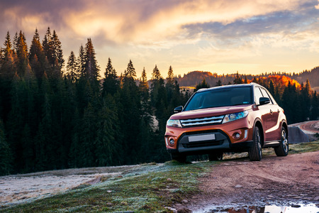 orange 4wd suv parked in mountain at sunrise. beautiful autumn scenery with gravel road through spruce forest. travel Europe by car concept