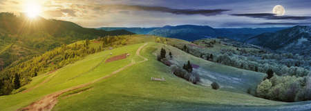 Foto de panorama of night and day time change above countryside. path down the grassy rural hills rolling in to the distance. ridge beneath an overcast sky with sun and moon in spring - Imagen libre de derechos