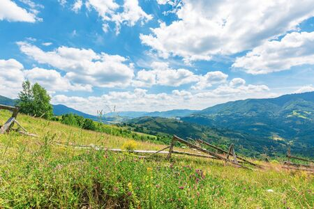 Photo pour wonderful landscape of rural area at noon.  amazing cloudscape above the distant mountain ridge. beautiful sunny weather. wooden fence on the grassy meadow - image libre de droit