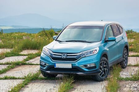 mnt. runa, ukraine - jun 22, 2019: popular family SUV in mountains on a cloudy day. 4th generation of a honda cr-v, in blue color. all wheel drive vehicle on a paved platform. car adventure concept