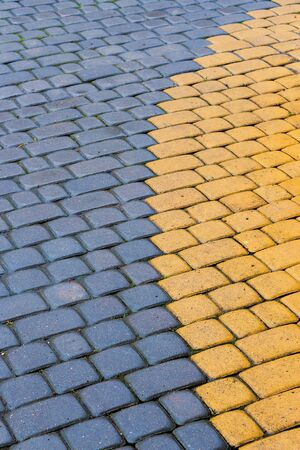 Photo for yellow and blue cobbles of pavement texture. stone masonry floor covering in arch form. top view of wet grungy background - Royalty Free Image