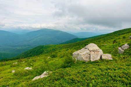 Photo pour boulders on the alpine hillside. view from the edge of a hill. beautiful summer landscape in mountains. overcast windy weather  with grey clouds on the sky - image libre de droit