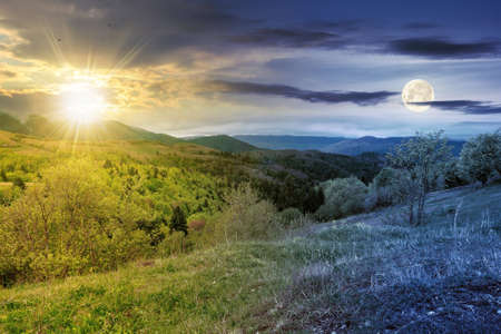 Foto de day and night equinox time change concept above mountainous countryside scenery in spring. trees and grass on hills rolling through green valley in to the distant ridge with sun and moon on the sky - Imagen libre de derechos