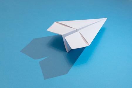 Foto de white paper plane with shadow on a blue paper background - Imagen libre de derechos