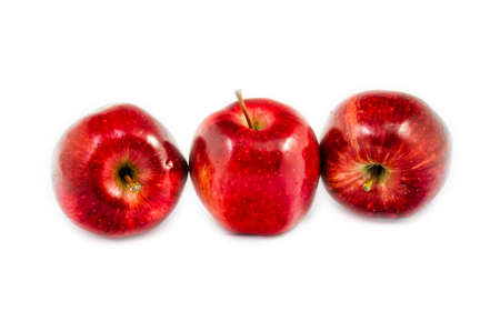 tree red apples in different put lied on