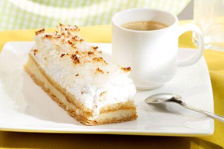 Photo pour Coconut cream cake on a white plate with a coffee cup - image libre de droit