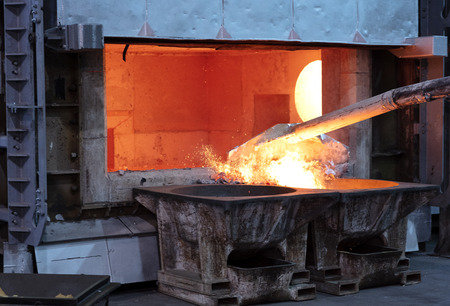 Photo pour skimming melted aluminum for removing the dross before casting. Aluminum foundry works showing an open furnace - image libre de droit