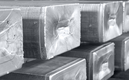 Photo pour heavy aluminum ingots stacked in a warehouse foundry, raw material to be processed in a hot mill. Photo in black and white with bluish tone - image libre de droit