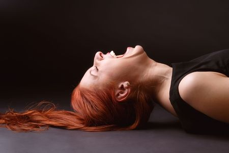 Red-haired woman laying on her back on the floor and laughing like mad