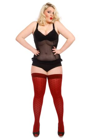 Humorous shot of beautiful blond plus-size woman in sexy lingerie and stockings