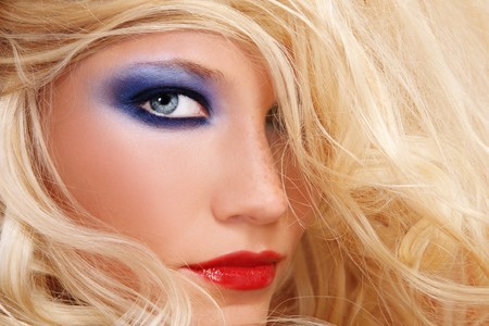 Close-up shot of young beautiful woman with long blond hair and stylish make-up
