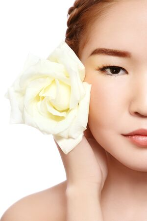 Close-up portrait of young beautiful asian girl with rose on white background