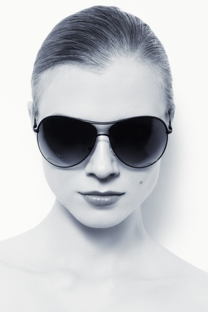 Portrait of young woman in stylish sunglasses over white wall