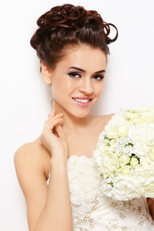 Portrait of young beautiful smiling bride with stylish make-up and hairdo over white wall