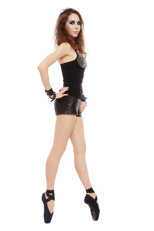 Young slim beautiful girl in spiked top and ballet shoes dancing on white background