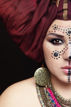 Close-up portrait of young beautiful woman with traditional Berber face paint and turban