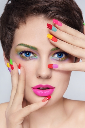 Photo pour Close-up portrait of young stylish beautiful girl with fancy make-up and colorful french manicure - image libre de droit