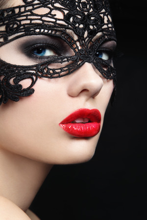 Close-up portrait of young beautiful stylish woman in black lacy maskの写真素材