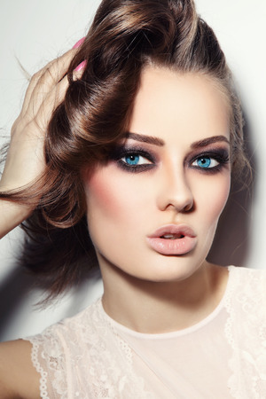 Photo for Portrait of young beautiful blue-eyed woman with stylish make-up touching her hair - Royalty Free Image