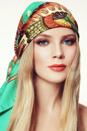 Portrait of young beautiful woman with long hair and stylish smoky eyes make-up in green silk scarf