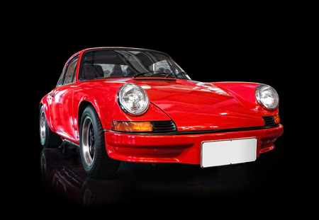 Red classic sports car isolated on black background