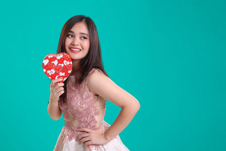 Attractive young Asian lady in elegant vintage dress posing with heart shaped gift box, isolated over turquoise background for Valentines concept