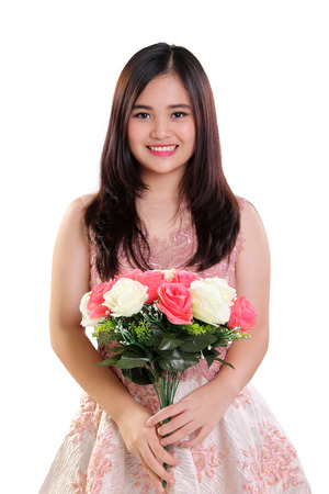 Portrait of happy beautiful Asian teenage girl holding a bouquet of roses, isolated on white background