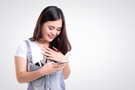 Photo pour Attractive Asian teenage girl looking at her mobile phone screen with joyful face, on white background for copy space - image libre de droit