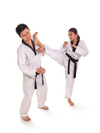 Foto de Female fighter kicking her male opponent right on the face, full length portrait on white background - Imagen libre de derechos