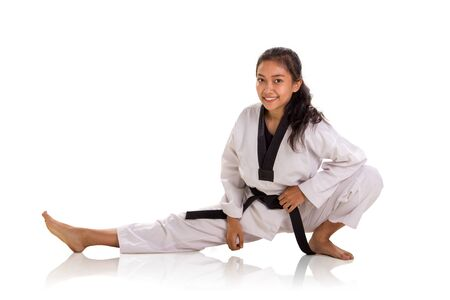 Photo pour Cheerful female fighter doing physical training, stretches her right leg straight during warm up. Studio shot, portrait over white background - image libre de droit