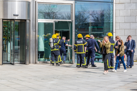 A group of firefighters outside a building. Dublin, Ireland - April 21, 2016: Group of firefighters from Dublin Fire Brigade gathered outside a building.  Firefighters talking. People passing by.
