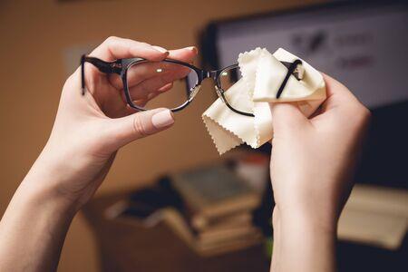 Photo pour Female hands rubs black-rimmed spectacles special sponge - image libre de droit