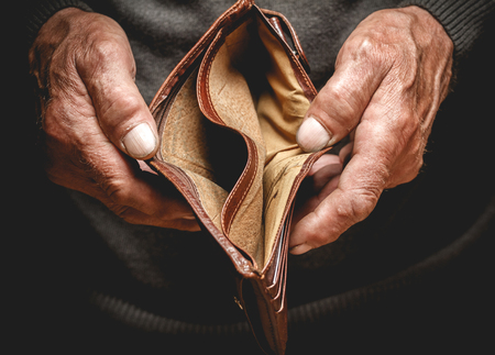 Photo pour Empty wallet in the hands of an elderly man. Poverty in retirement concept - image libre de droit