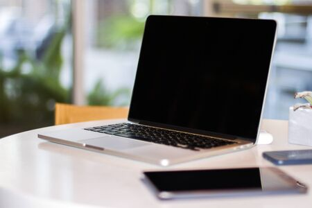 Foto de Close up of modern laptop with blank screen on white table in sunny interior, mockup. Business and technology concept - Imagen libre de derechos
