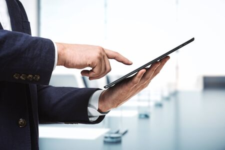 Photo pour Man presses on the screen of a digital tablet in sunny boardroom, close up. Online technology concept - image libre de droit