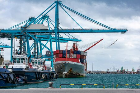 Photo for Tugboats and container ship moored at the dock - Royalty Free Image